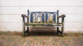 Använd gammal bänk framme av det vita wood vägganseendet på kullersten i stadsområde Arkivfoto