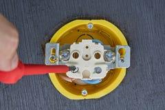 Använd hand-rymde den phillips skruvmejseln för att reparera väggen elektrisk soc royaltyfria foton