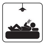 Använd smartphonen eller minnestavlan på sängsymbolen Arkivbild