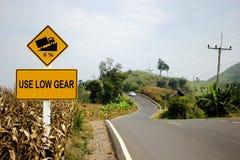 Använd trafiktecknet för det låga kugghjulet på vägen i berg Arkivfoton