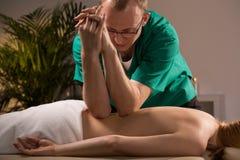 Använda armbågar under massage arkivbilder