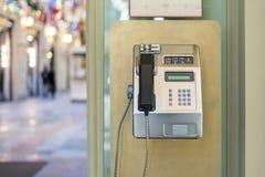 Använda av den offentliga payphonen gammal payphone i gatan f arkivfoto
