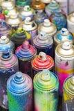 Använda cans av sprutmålningsfärg Arkivfoto