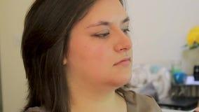 Använda den lilla borsten för att applicera eyeliner till den unga kvinnan arkivfilmer