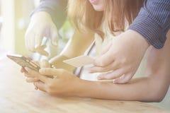 Använda den smarta telefon- och innehavkreditkorten som online-shopping arkivbilder