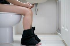 Använda den smarta telefonen i toaletten Arkivbilder
