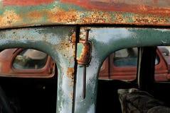 Använda en grov spik som ett gångjärnstift i en gammal rostig bil royaltyfria foton