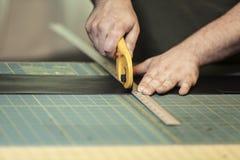 Använda en roterande läderskärare på en Grided skärbräda royaltyfri bild