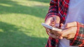 Använda en smart telefon i parkera royaltyfri bild