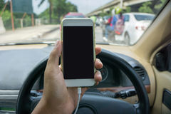 Använda en smartphone, medan köra en bil Fotografering för Bildbyråer