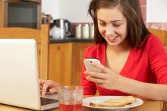 använda för mobil telefon för flickabärbar dator tonårs- Arkivbild