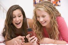 använda för mobil telefon för underlagflickor liggande tonårs- Arkivbilder