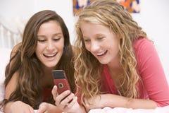 använda för mobil telefon för underlagflickor liggande tonårs- Royaltyfri Fotografi