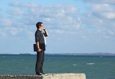 använda för telefon för strandbärbar datorman Arkivfoto