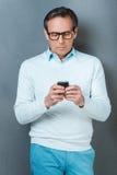 Använda hans telefon för att vara i handlag Royaltyfri Bild