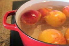 Använda kokande vatten för att lossa persikahudar Royaltyfri Fotografi