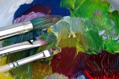Använda målarfärgborstar är på den målade yttersidan fotografering för bildbyråer