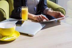Använda mobila enheter i kafé Arkivfoto