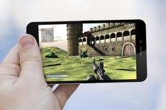 Använda mobiltelefonen för att spela Royaltyfri Fotografi