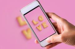 Använda mobiltelefonen för att ta foto av kakaabc:et i form av ordet FÖRÄLSKELSE på rosa bakgrund, valentindag Arkivbild