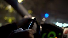 Använda smartphonen, medan köra på natten i staden arkivfilmer
