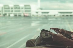 Använda telefonen på flygplatsen Kvinnahänder som rymmer den smarta telefonen, defocused flygplan och terminalen Tonad bildtappni royaltyfri foto