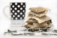 Använda tepåsar och en kopp Arkivfoton