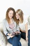 användande kvinnor för datortablet två Royaltyfri Foto