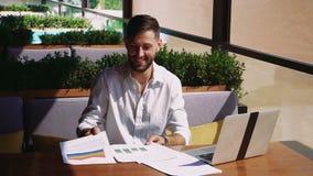 Användbar chef som tycker om kallt resultat och arbete med bärbara datorn på tabellen lager videofilmer