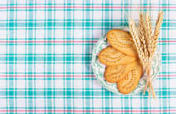 Användbara sädes- kex och veteöron på en rutig bordduk Hem- frukost Arkivfoton