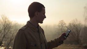 Använder den caucasian grabben för den lyckliga rödhåriga mannen en smart telefon i parkerar med träd i bakgrunden och gör en sel stock video