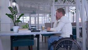 Använder den handikappade mannen för pensionären i hjulstol som sitter på tabellen med koppen kaffe som talar på mobiltelefonen o stock video