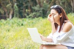 Använder kvinnor bärbara datorn, och hon ögat smärtar royaltyfria bilder