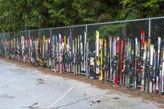 Använt gammalt skidar och snöbräden som förläggas mot ett staket arkivfoton