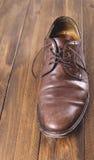 Använt och smutsa ner den bruna skon på den bruna trätabellen Fotografering för Bildbyråer
