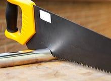 använt trä för cuttingmetallrør saw Arkivfoto