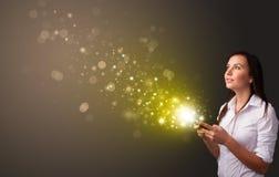 Anv?nda telefonen med guld- mousserande begrepp fotografering för bildbyråer