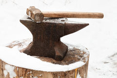 Anvil with hammer in old abandoned village smithy. In winter Stock Images
