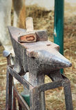Anvil and hammer. Old anvil with hammer on a metal stump Stock Image