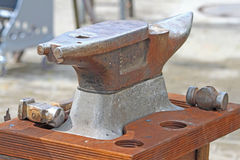 Anvil with hammers. An heavy anvil with two hammers royalty free stock photography