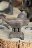 Anvil. Rusty hammer anvil on a wooden block in front of blacksmith products Stock Photo