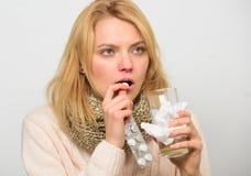 Anvisningar för behandling av förkylning Flickan tar medicindrinkvatten Huvudvärk- och förkylningboter För hårhalsduk för kvinna  fotografering för bildbyråer