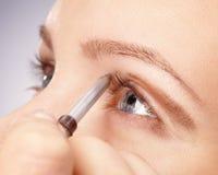 Anwenden der Augenschminke für junges Mädchen stockfoto