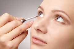 Anwenden der Augenschminke für junges Mädchen lizenzfreies stockfoto