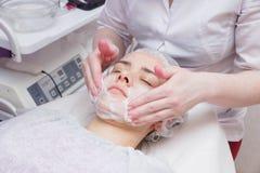 Anwenden des Schaums am Gesicht des Mädchens vor dem mesotherapy Verfahren lizenzfreies stockbild