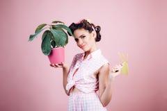 Anwenden von Sorgfalt für Umwelt Gewächshausarbeitskraft oder -gärtner Stift herauf Frau mit modischem Make-up Frühling Pinupmädc stockfotos