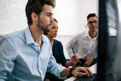 Anwendungsentwickler, die an Computern im Büro arbeiten lizenzfreie stockfotos