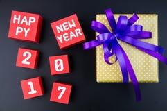 Anwesende Geschenkbox und Zahl des guten Rutsch ins Neue Jahr 2017 auf rotem Papierkasten Lizenzfreies Stockbild