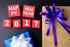 Anwesende Geschenkbox und Zahl des guten Rutsch ins Neue Jahr 2017 auf rotem Papierkasten Stockfotografie