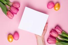 Anwesende Karte des weiblichen Handgriffs auf einem rosa Hintergrund mit Blumen und Ostereiern lizenzfreie stockbilder